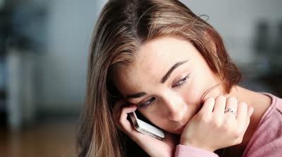 Stock-footage-depressed-woman-contemplates-suicide-as-she-hears-bad-news-over-the-phone-at-home