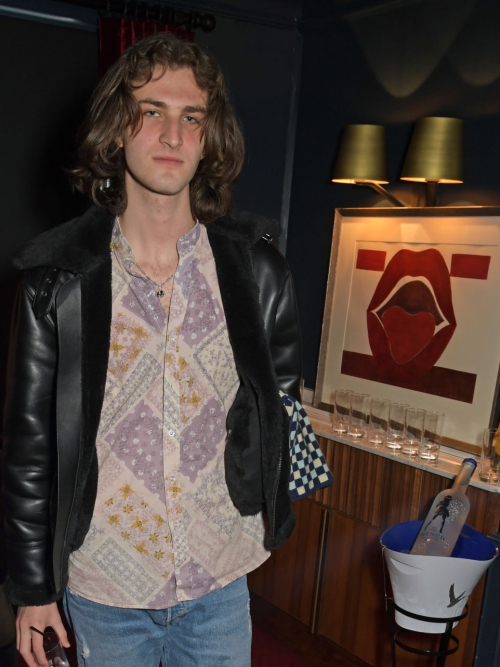 Roman Lewis poses in front of artwork by Emilia Salcedo at Christabel's launch.